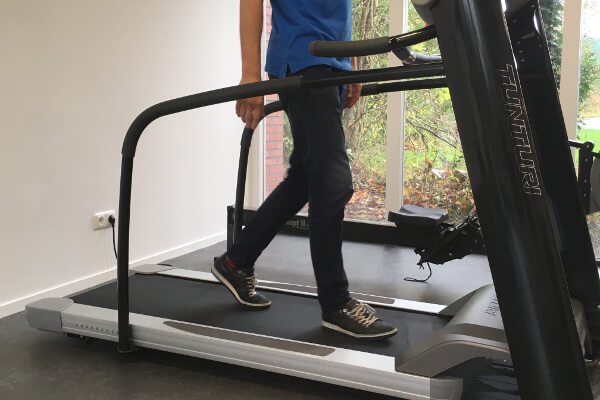 Man met Claudicatio op loopband voor behandeling etalagebenen - Fysio 4 Groningen
